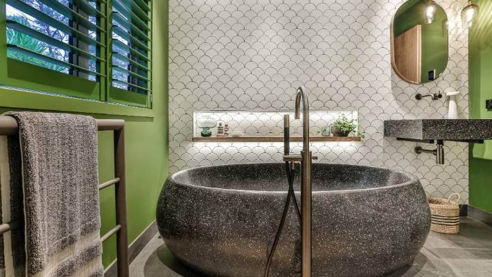 Matt and gloss fan tiles are teamed with a crushed marble bathtub and vanity top in this NKBA award-winning bathroom designed by Natalie Du Bois.