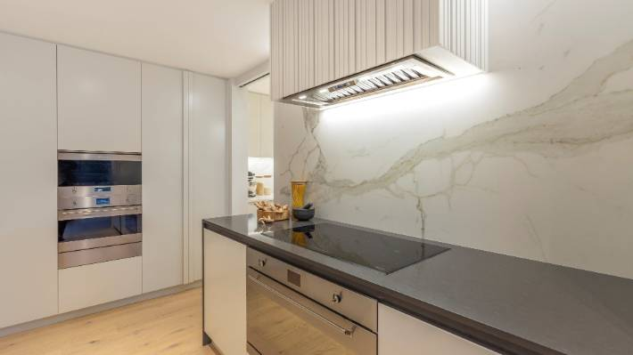 Large porcelain sheeting that replicates  marble features on the splashback in this kitchen designed by Natalie Du Bois.