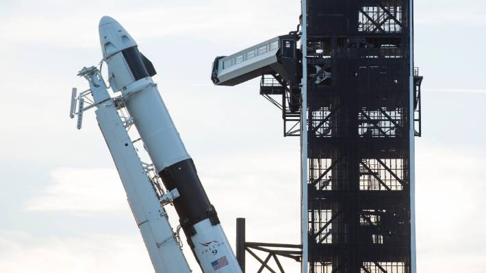 A SpaceX Falcon 9 rocket with the company's Crew Dragon spacecraft onboard is seen as it is raised into a vertical position on the launch pad at Launch Complex 39A