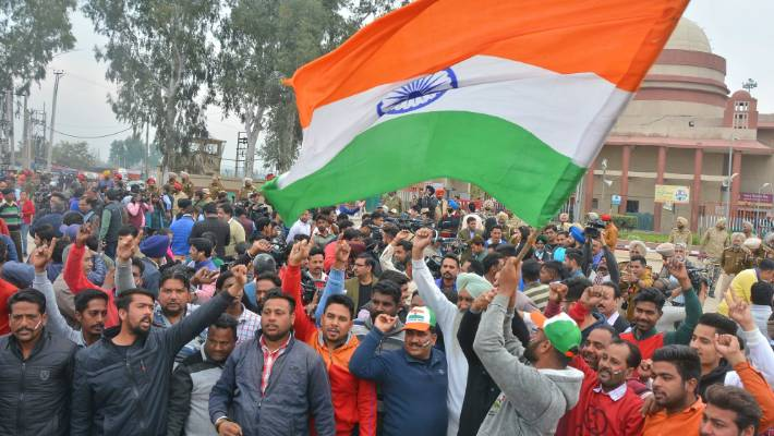 An Indian waves a national flag as others shout slogans while they wait to welcome the captured Indian pilot home at the India-Pakistan border.