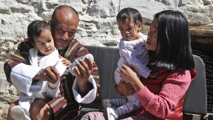 Nima and Dawa sit with their mother Bhumchu Zangmo and father Sonam Tshering at the Tachog Lhakhang Buddhist temple.