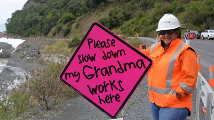 Christchurch Grandma Chantel Owen with her new signs on State Highway 1 near Kaikōura.