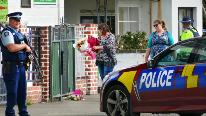 Armed police guard a Invercargill Mosque as sisters Ruth Sears, and Jenny South lay flowers.