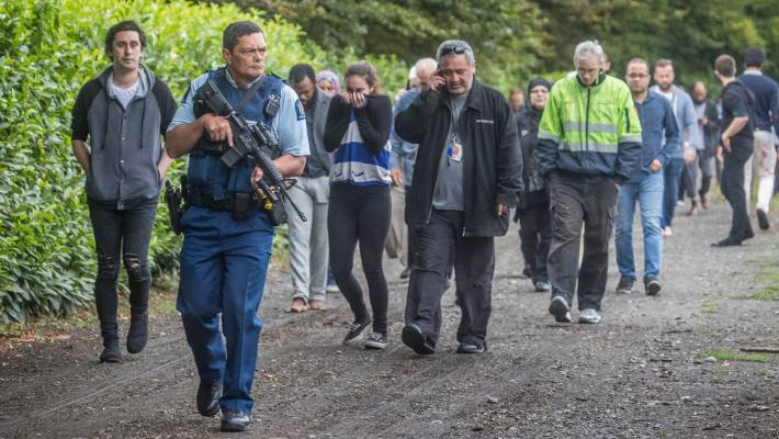 Armed police escort survivors to the hospital after the Christchurch mosque shooting