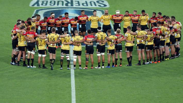 The Chiefs and Hurricanes players link arms on Friday before their game.