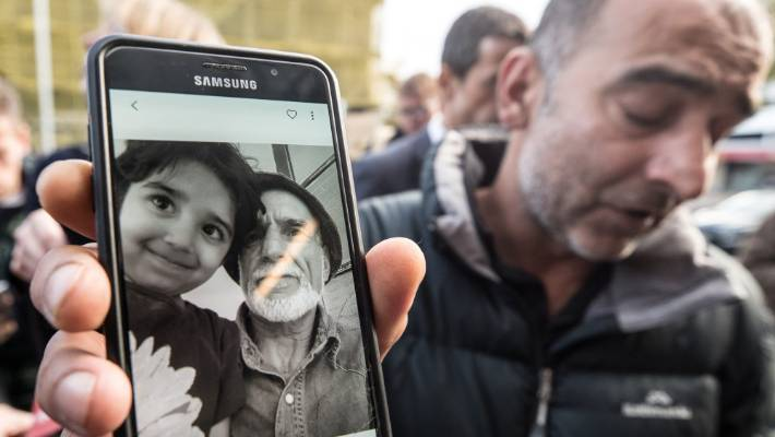 Yama Nabi holds a photo of his father , 71-year-old Haji Daoud, who was killed in the Masjid Al Noor Mosque in Christchurch.