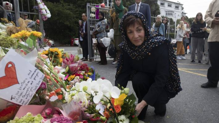 Governor General Dame Patsy Reddy lays down flowers as a tribute.