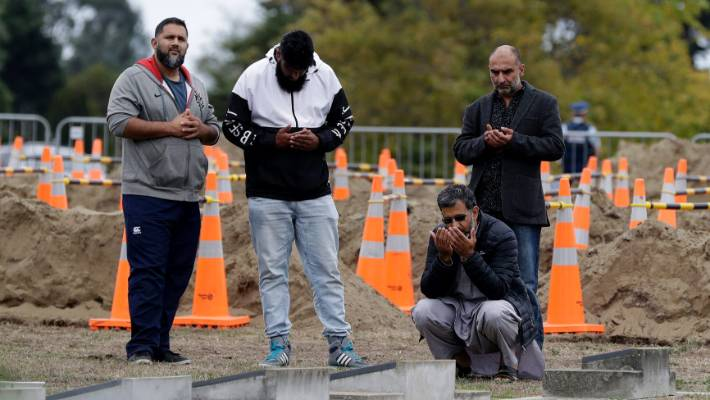Men pray at the Muslim cemetery in Christchurch, after 50 people died in Friday's mosque shootings.