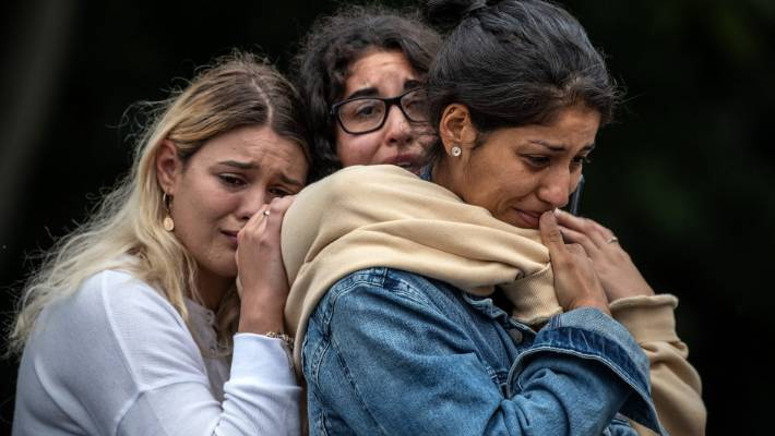Young women weep as they hold each other for comfort during a students' vigil near Al Noor mosque, after the shootings in Christchurch.