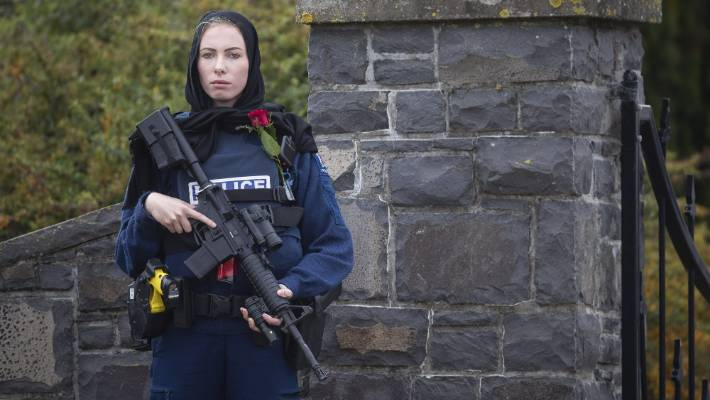 Police officer Constable Michelle Evans in hijab with a rifle and rose outside Christchurch Memorial Park Cemetery, as victims of the mosque shootings are buried.