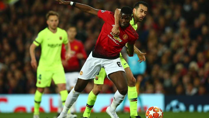 Barcelona's Sergio Busquets, right, vies for the ball with Manchester United's Paul Pogba.