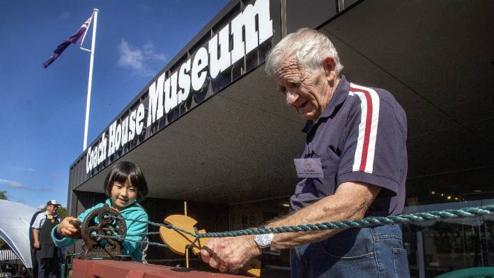 Koharu Tsutsumi, 8, from Palmerston North, tries her hand on an old-time rope platting machine, with museum custodian Joe Beattie.
