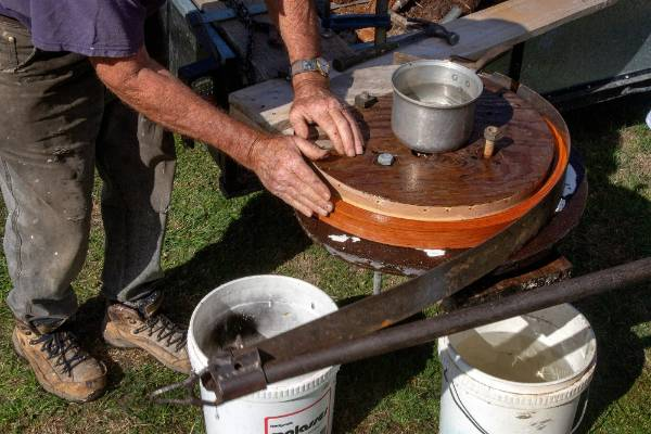 Vern Jensen checks the one inch thick strip of hickory bent to form the wheel rim for a Model T Ford. vintage car.