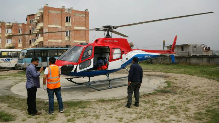 Hospital officials get ready to unload the dead body of a plane crash victim outside the Teaching Hospital in Kathmandu Nepal Sunday