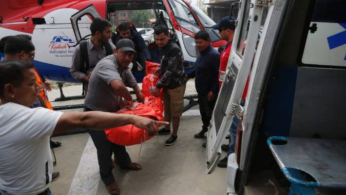 Hospital officials unload the dead body of a plane crash victim outside the Teaching Hospital in Kathmandu Nepal Sunday
