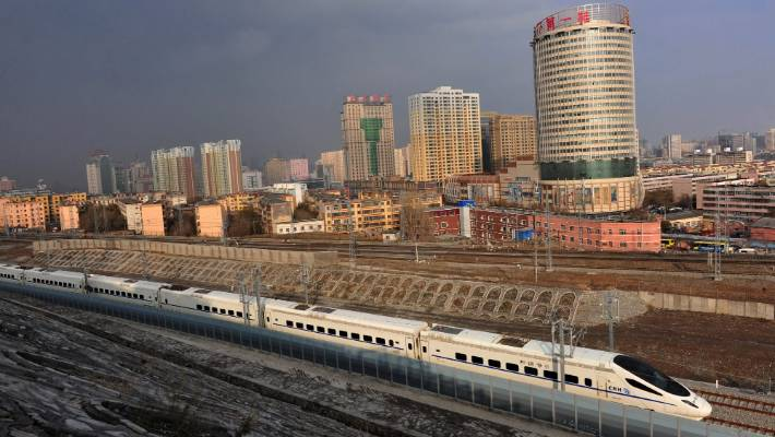 A CRH high-speed train runs across Urumqi city.