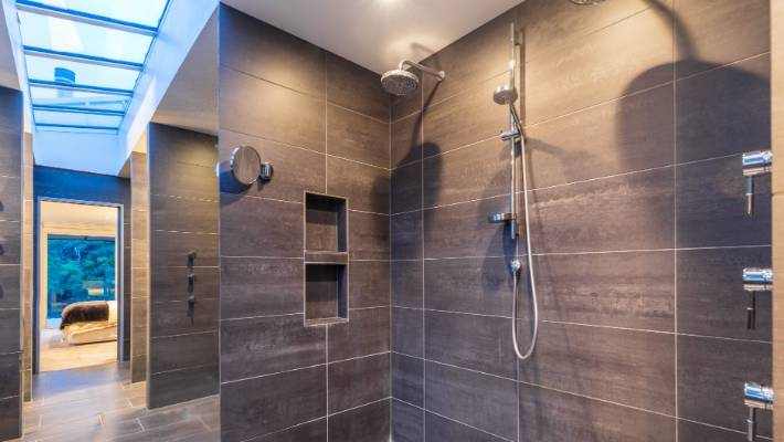 The huge triple shower in the master ensuite with the master bedroom in the background.