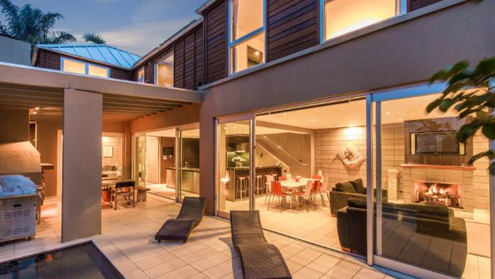 Sliding glass doors open onto an outdoor entertaining area with a large BBQ oven, open fireplace, 10-seater teppanyaki table, spa pool, loungers and a reflection pool.