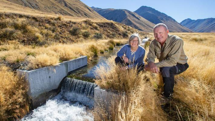 Sam Staley, range warden of the Tekapo Military Training Area with Minister of Conservation, Eugenie Sage at a weir designed to stop trout in one of the spring fed streams.