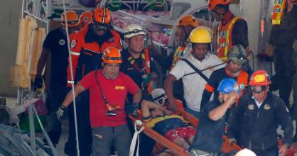 Rescuers carry a survivor out from the rubble of a commercial building following a 6.1 magnitude earthquake on Easter Monday.