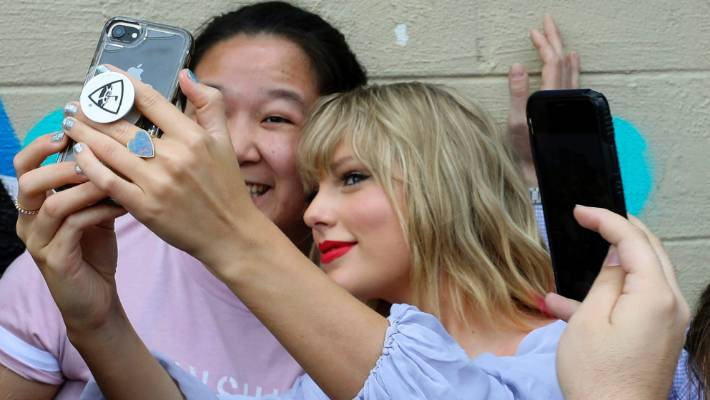 Taylor Swift snaps a selfie with a fan at a butterfly mural in Nashville.