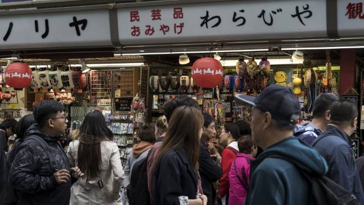 Tourists walk past stores in Asakusa area. Service workers aren't getting a break.