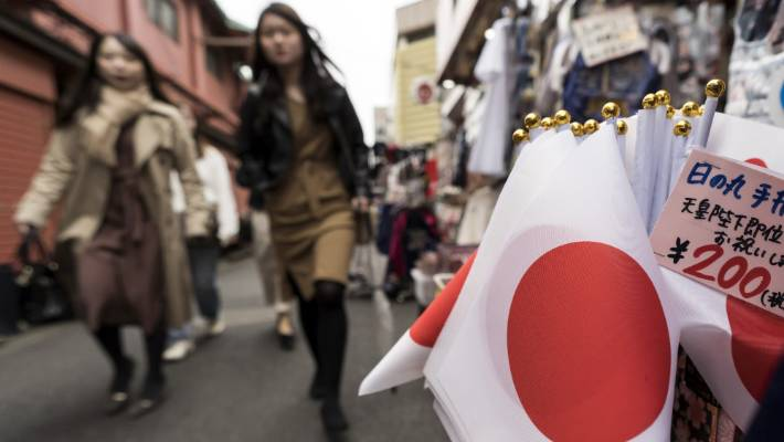 Tourists pass through Japanese national flags displayed for sale in front of a shop in the Asakusa area on the first day of the Golden Week holiday.