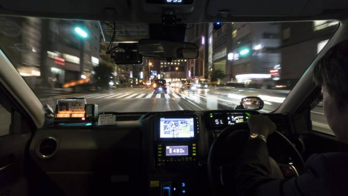 A taxi driver drives his cab at night in Tokyo, Japan. The nation's travel industry expects to increase in bookings for trips.