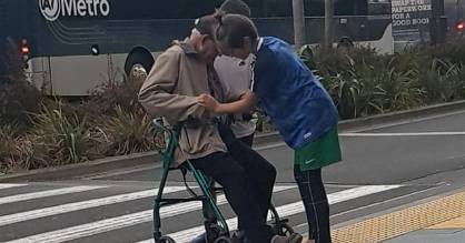 Friends Blake Osklestan and Daniel Coyle-Smith help the man cross the road in New Lynn, Auckland.
