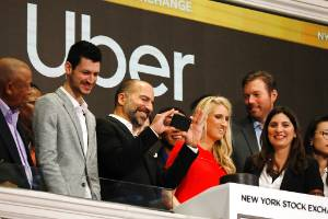 Uber CEO Dara Khosrowshahi, third from left, takes a photograph as he attends the opening bell ceremony at the New York ...