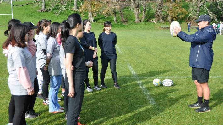 Tourism businesses are being urged to cater for International students coming here to study. This group of young Asian women are attending a Have A Go Rugby session in Auckland.