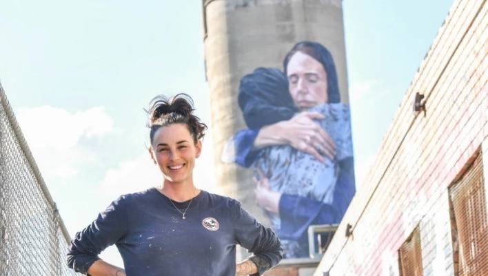 Peace, love and understanding: Artist Loretta Lizzio in front of the Jacinda Ardern mural in Melbourne.