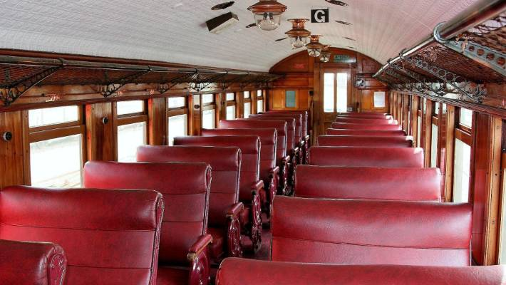 The Marlborough Flyer carriages feature varnished wood interiors, wrought-iron luggage racks, sliding windows, brass lamps and red vinyl upholstery.