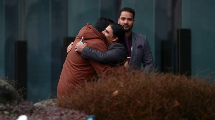 Linwood mosque hero Abdul Aziz hugs a friend outside the Christchurch court house.
