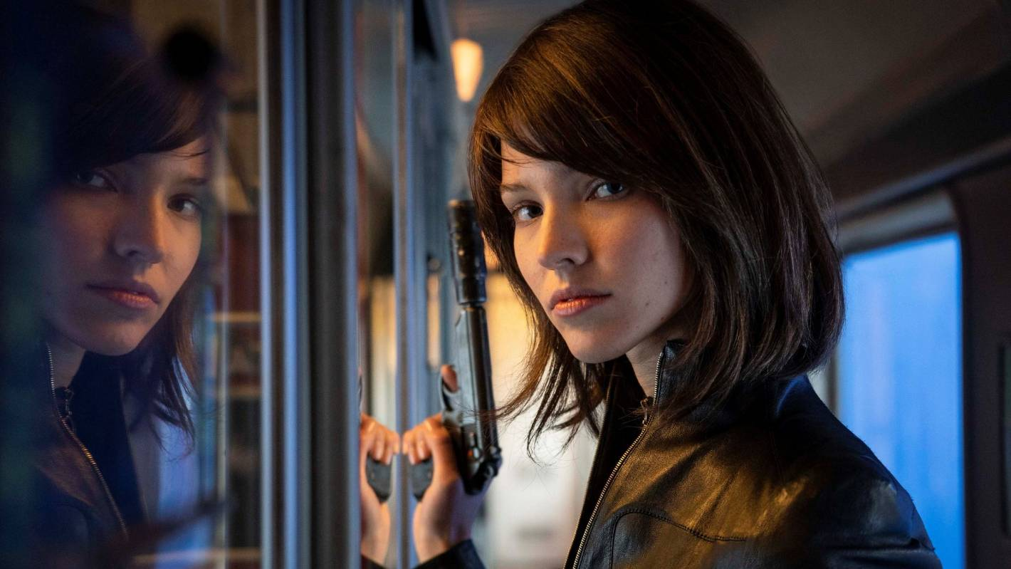 Anna holding a gun, staring into the camera with a brunette wig on