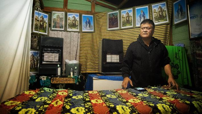 Nga Teina beside the bed where he treats his clients. He has set up a studio in the yard of his south Auckland home.