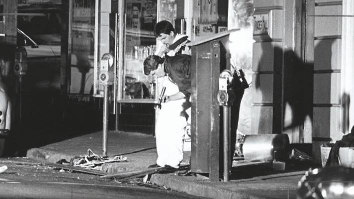 Detectives inspect the Trades Hall bombing scene the day after the explosion.