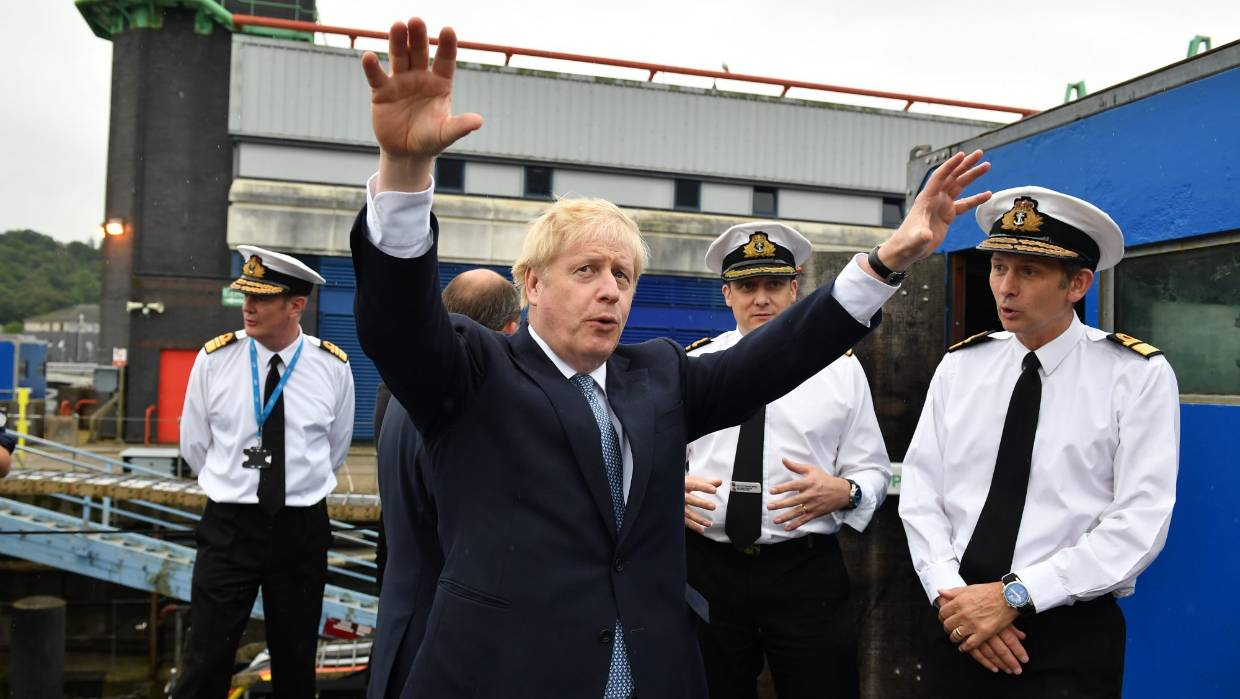 "Boris Johnson, here visiting HMS Victorious at Naval Base Clyde in Faslane, Scotland, ""revels in being on stage, spot-lit, the adults all paying him attention"", writes Joe Bennett. — Photograph: Getty Images."