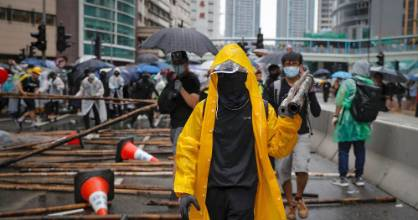 Demonstrators carry in bamboos sticks to block a road.