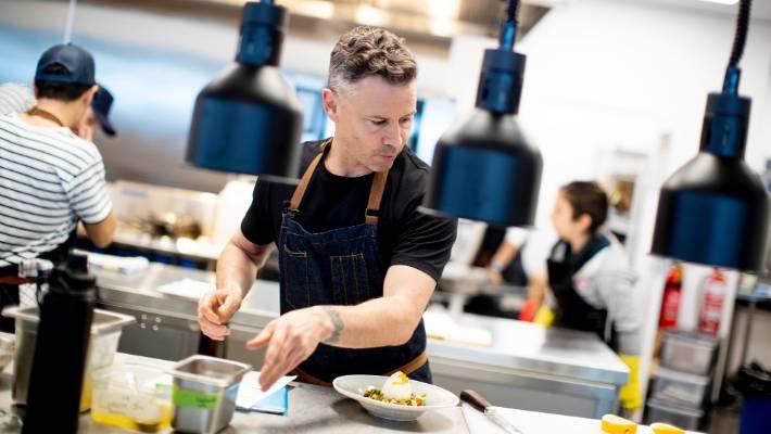 Nic Watt in action in Akarana Eatery's open kitchen.