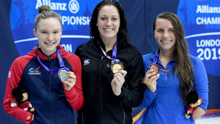 New Zealand's Sophie Pascoe, centre, shows off her medal after winning the women's 100m butterfly S9.