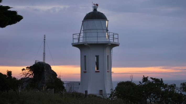 The sun setting behind the Baring Head. Atmospheric carbon measurements are still taken there to this day.