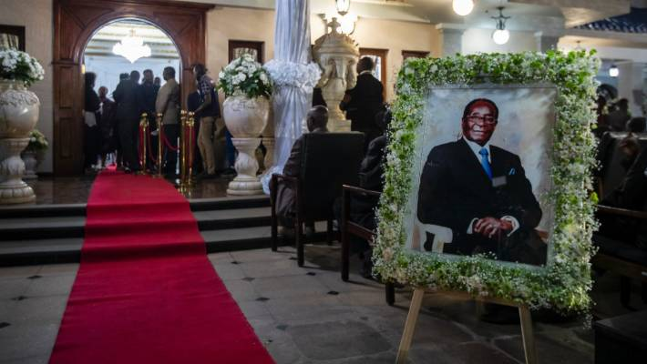 A portrait of former president Robert Mugabe stands outside the room where his body lies in state.