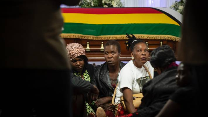 Mourners sit around the body of former president Robert Mugabe, as he lies in state inside his official residence in the capital Harare, Zimbabwe.