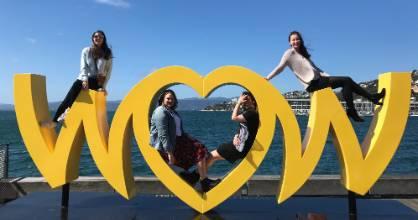 Sophia Reid, Rebecca Ley, Sam Haywood, and Ellen McNamara pose on the World of WearableArt sign on the Wellington waterfront.