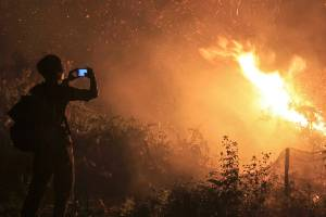 A man takes photos of a forest fire in Kampar, Riau province, Indonesia.