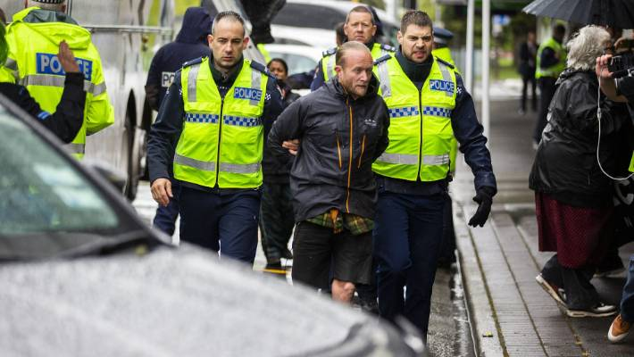 A weapons expo protestor is arrested after he was ordered down off the roof of a bus by police on Fitzherbert St, Palmerston North, on day two of the defence forum in 2018.