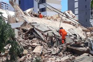 Firefighters search for people who are trapped after a building collapsed in Fortaleza.