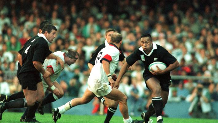 All Blacks captain Sean Fitzpatrick leads the support runners as Jonah Lomu rampages through England in the 1995 Rugby World Cup semifinal.