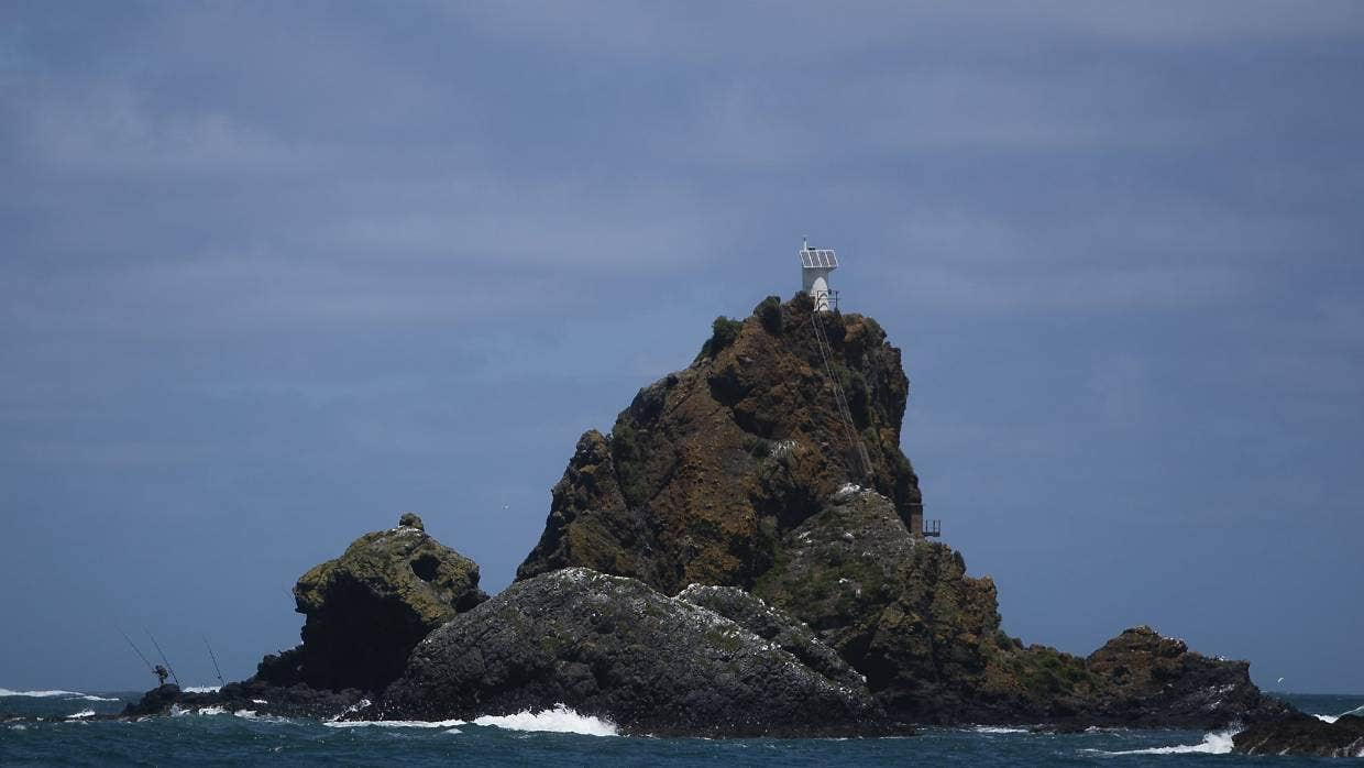 A fisherman was swept away from Te Toka-Tapu-a-Kupe/Ninepin Rock at Whatipu on Sunday.